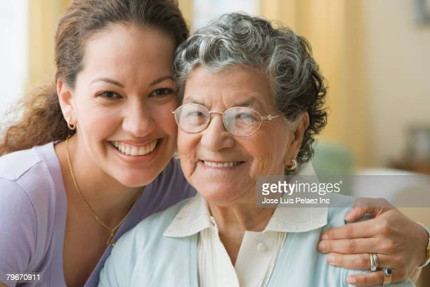 Hispanic mother and adult daughter hugging