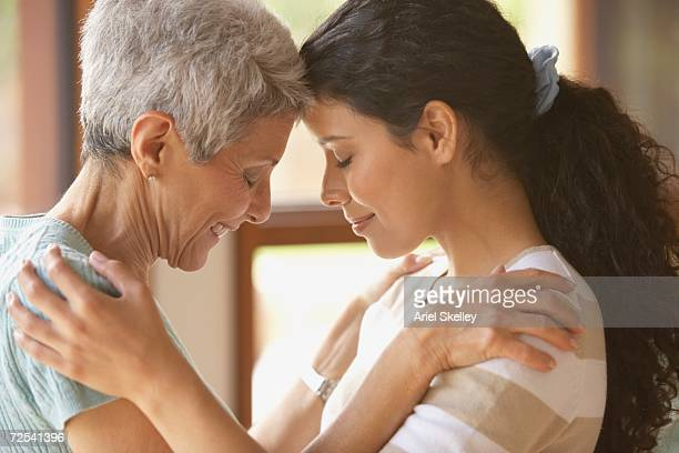 Hispanic mother and adult daughter touching foreheads
