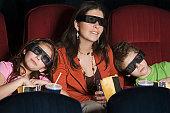 Hispanic mother and children watching 3D movie