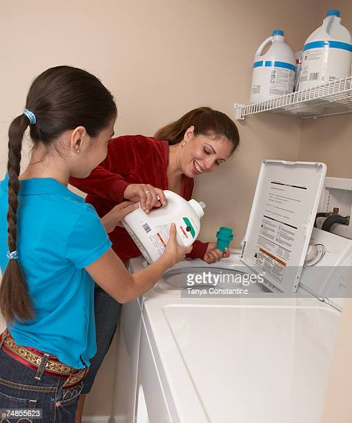 Hispanic mother and daughter doing laundry