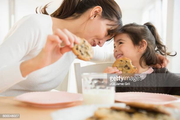 Hispanic mother and daughter eating together