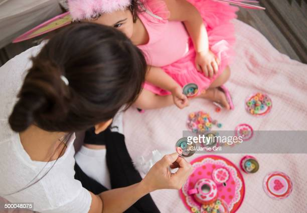 Hispanic mother and daughter having tea party
