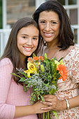 Hispanic mother and daughter holding flowers