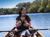Hispanic mother and daughter in canoe