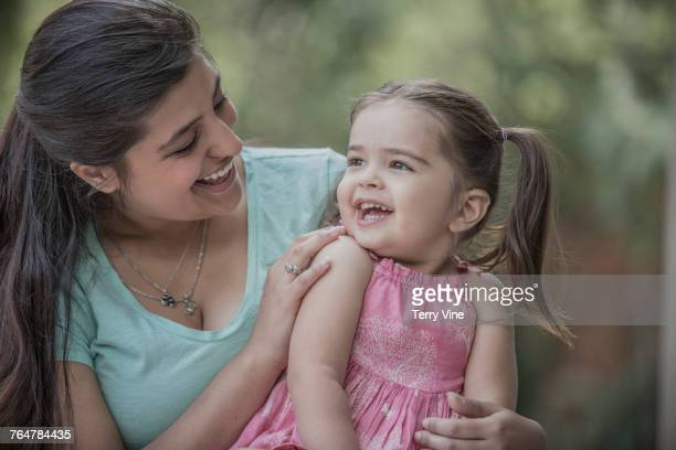 Hispanic mother and daughter laughing