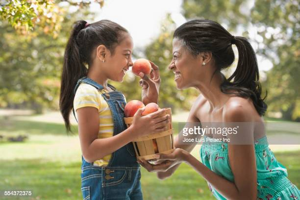 Hispanic mother and daughter picking apples in orchard