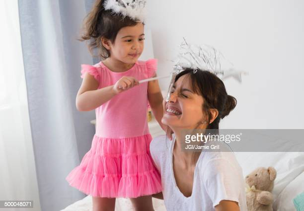Hispanic mother and daughter playing dress up on bed