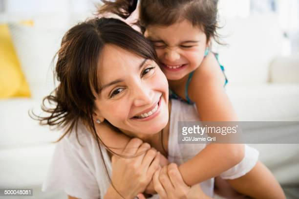 Hispanic mother and daughter playing in living room