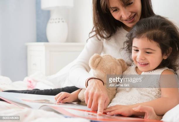 Hispanic mother and daughter reading in bed