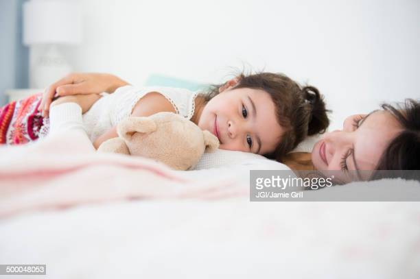Hispanic mother and daughter relaxing on bed