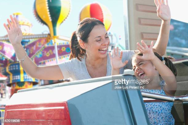 Hispanic mother and daughter riding roller coaster