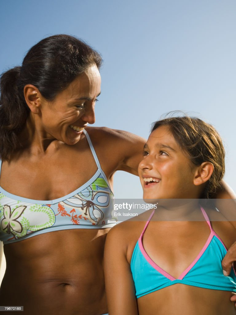 Hispanic mother and daughter smiling at each other : Stock Photo