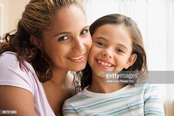 Hispanic mother and daughter smiling