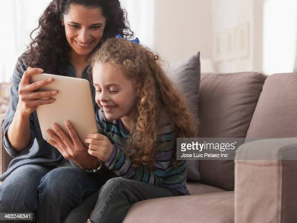 Hispanic mother and daughter using digital tablet