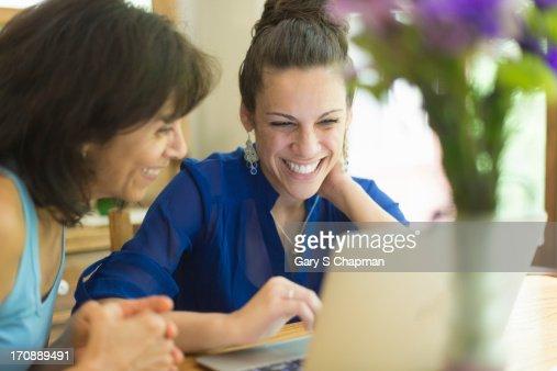 Hispanic mother and daughter using laptop : Stock Photo