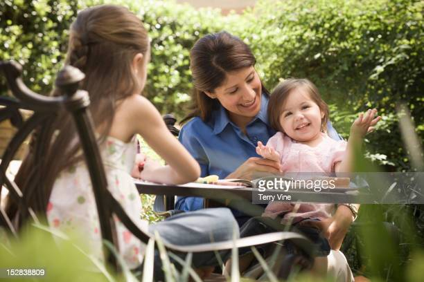 Hispanic mother and daughters sitting on patio