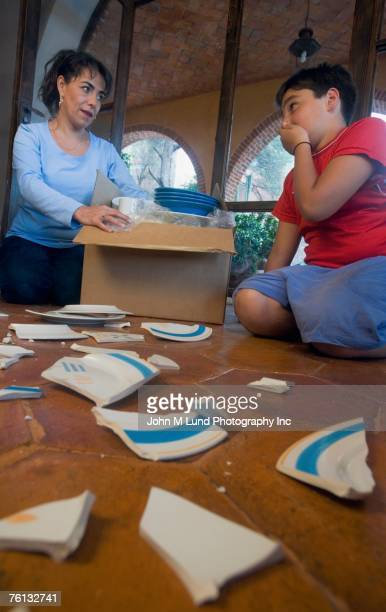 Hispanic mother and son next to broken plate