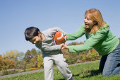 Hispanic mother and son playing football outdoors