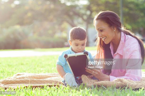 Hispanic mother and son reading in park