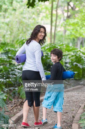 Hispanic mother and son walking with yoga mats in park