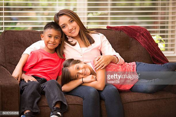 Hispanic mother and two children relaxing at home.