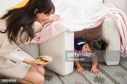 Hispanic mother bringing daughter cookies in fort
