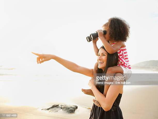 Hispanic mother carrying daughter with binoculars on beach