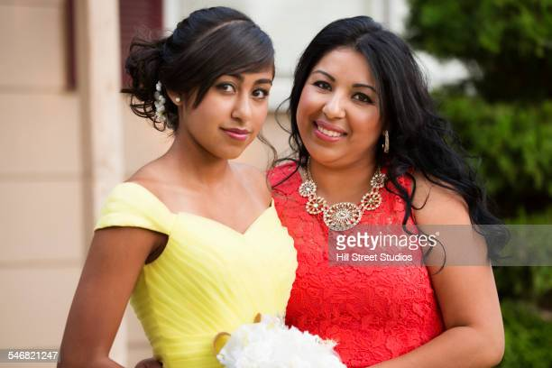 Hispanic mother celebrating quinceanera with daughter