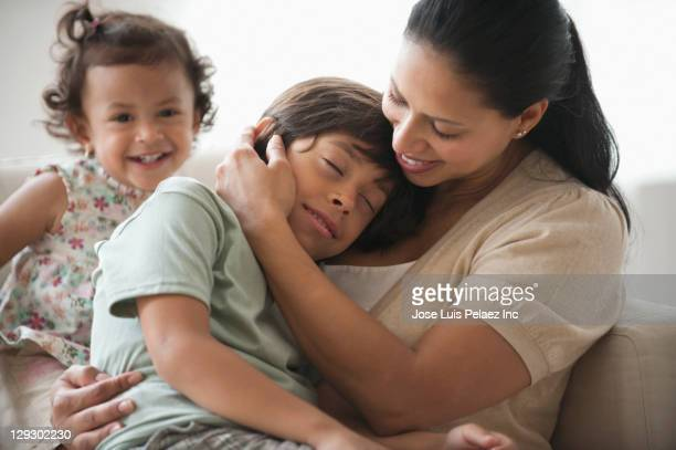 Hispanic mother comforting son