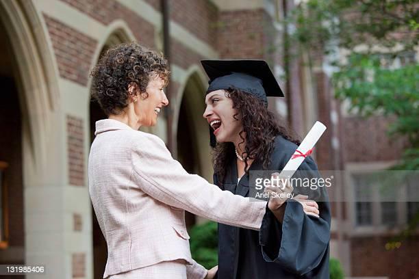 Hispanic mother congratulating graduating daughter
