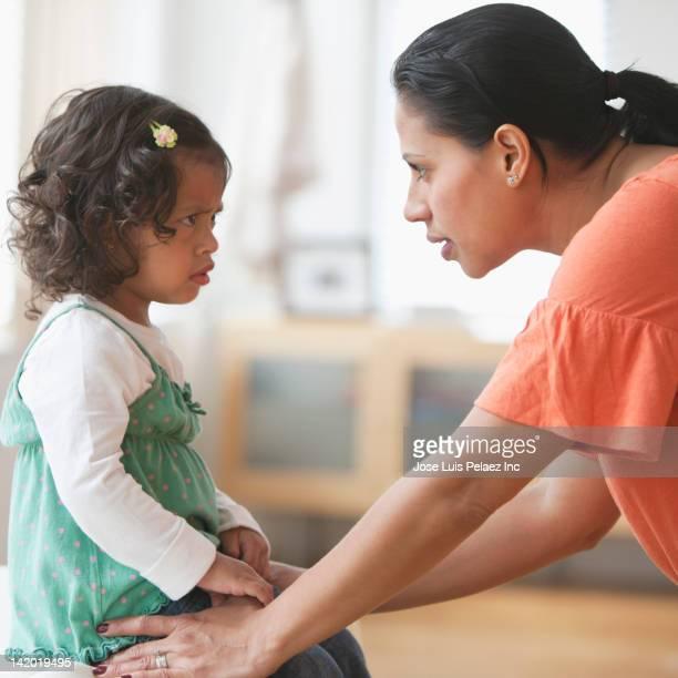 Hispanic mother disciplining daughter