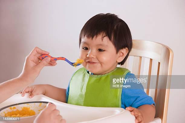 Hispanic mother feeding baby boy