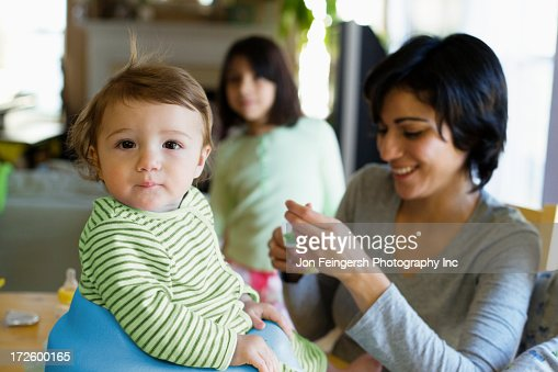 Hispanic mother feeding toddler in kitchen