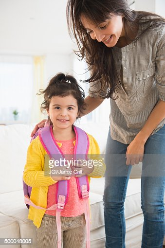 Hispanic mother getting daughter ready for school