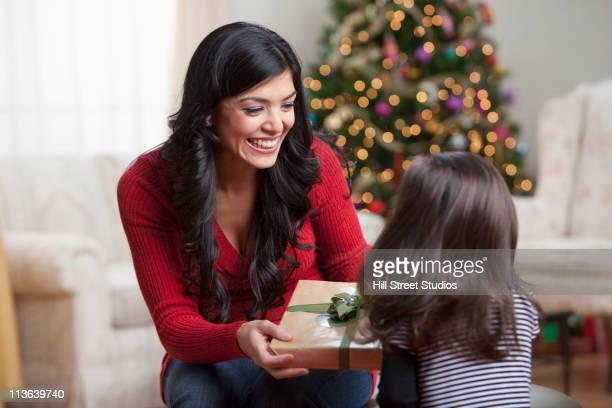 Hispanic mother giving daughter Christmas gift