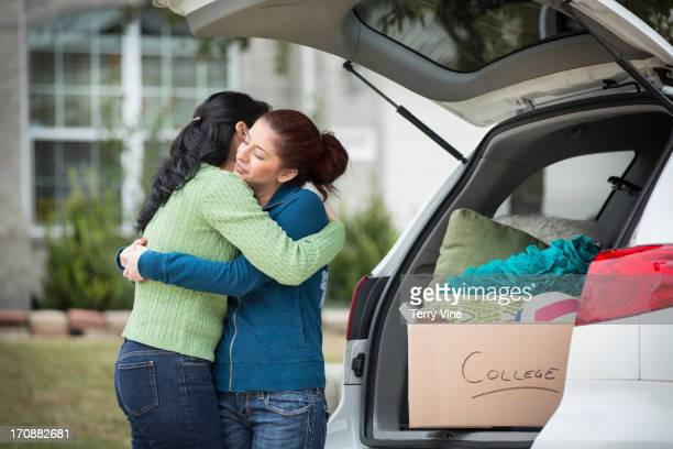 Hispanic mother helping daughter pack for college