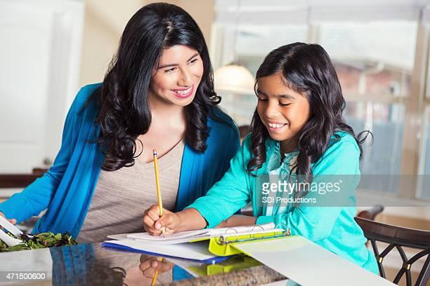 Hispanische Mutter hilft Tochter mit den elementaren Hausaufgaben