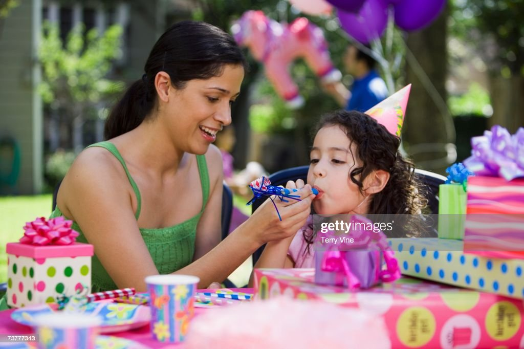 Hispanic mother helping daughter with noisemaker at outdoor birthday party : Stock Photo