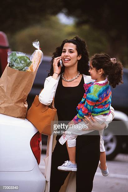 Hispanic mother holding daughter and using cell phone next to grocery bag outdoors