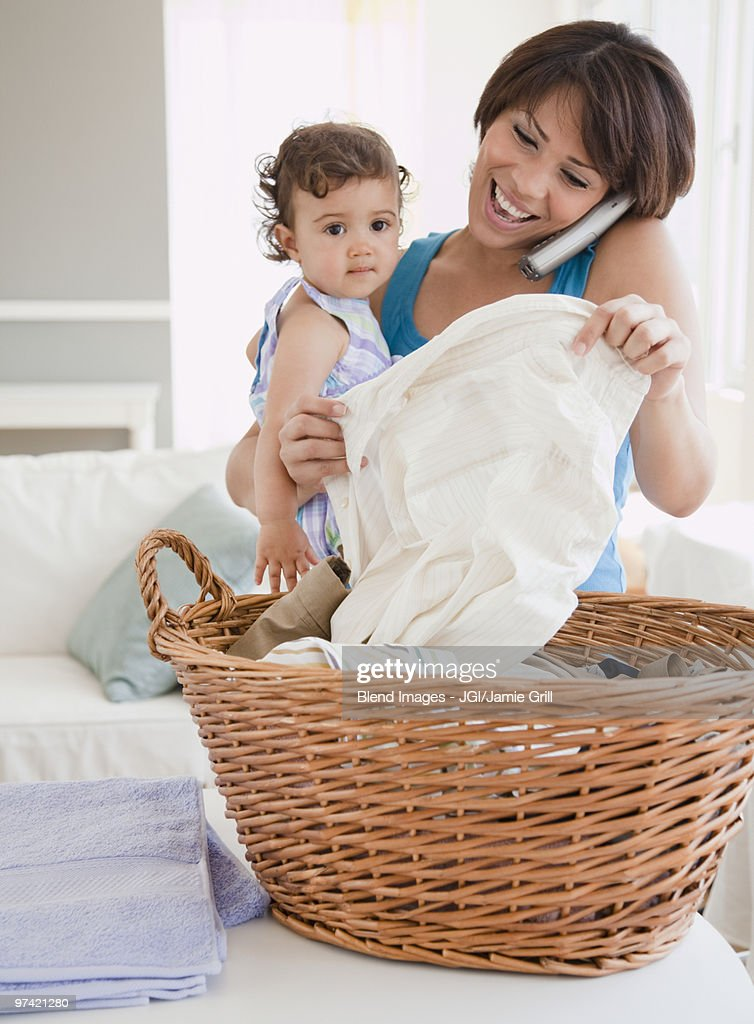 Hispanic mother holding daughter, talking on phone and doing laundry : Stock Photo