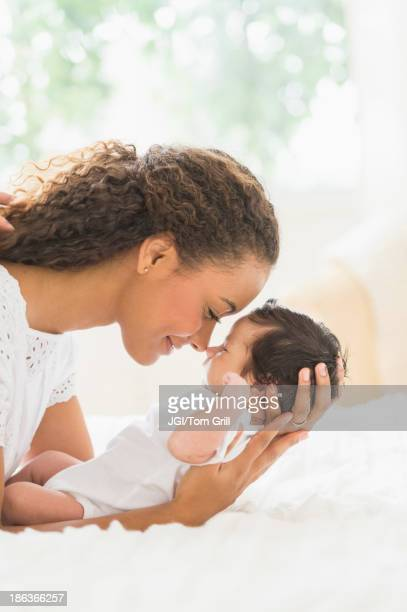 Hispanic mother holding infant on bed