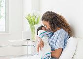 Hispanic mother holding newborn in hospital