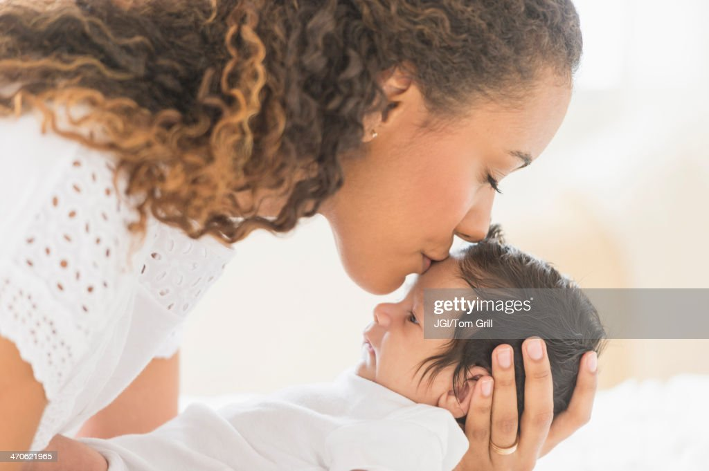 Hispanic mother kissing baby's forehead
