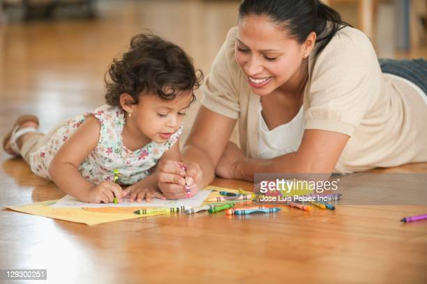 Hispanic mother laying on floor drawing with daughter