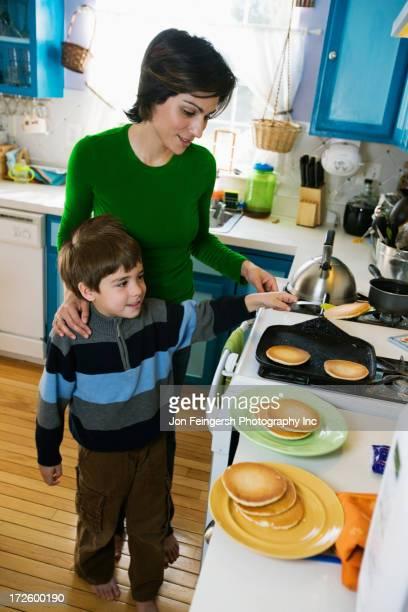 Hispanic mother making breakfast for son