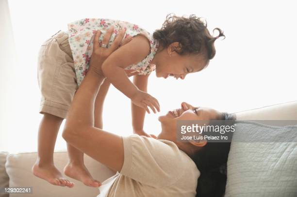 Hispanic mother playing with daughter on sofa