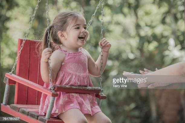 Hispanic mother pushing daughter in wooden swing