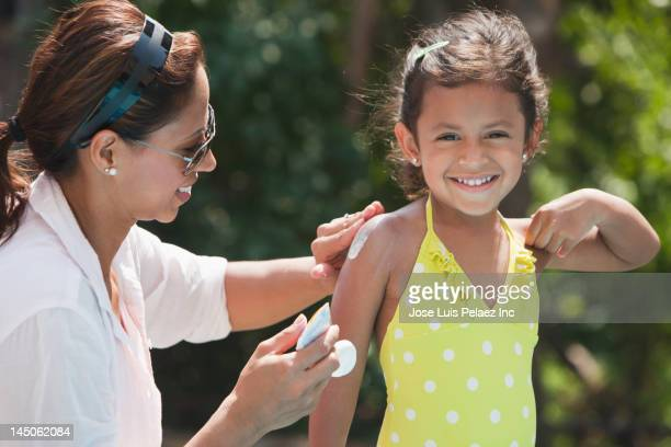 Hispanic mother putting sunscreen on daughter