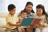 Hispanic mother reading to children