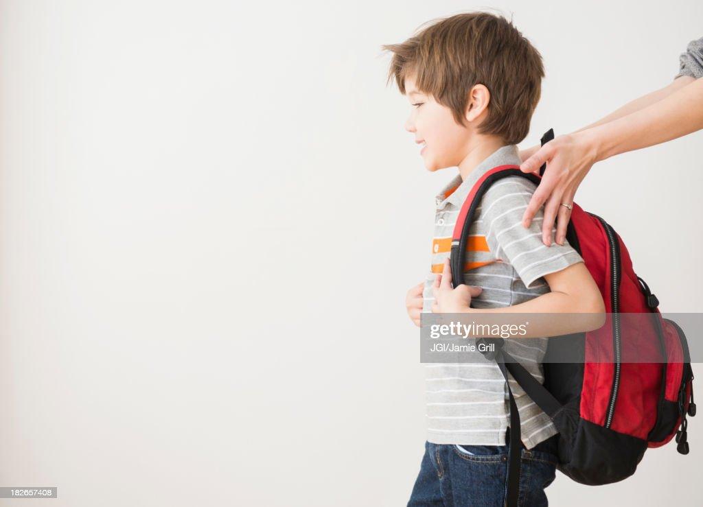 Hispanic mother rushing son to school : Stock Photo